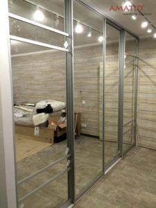 Встроенный шкаф-купе в гостиной с зеркальными дверьми.